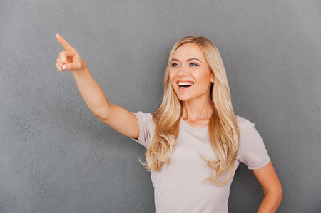 blond hair: Happy young blond hair woman pointing and looking away while standing against grey background