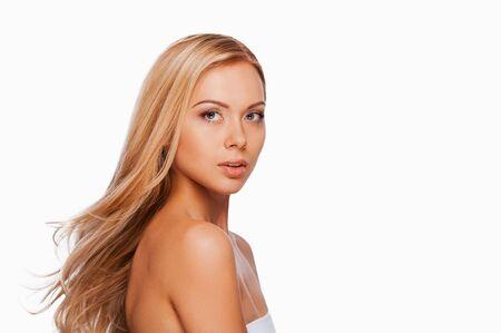 cabello rubio: Vista lateral de la joven y atractiva mujer de pelo rubio mirando a la cámara mientras está de pie contra el fondo blanco