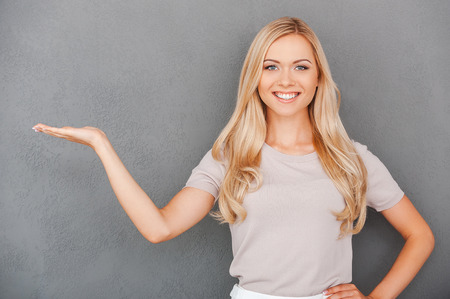 Smiling young blond hair woman holding copy space and looking at camera while standing against grey background