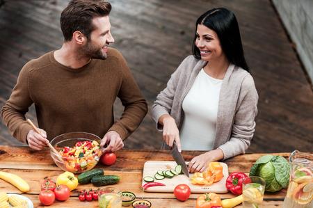 一緒に料理を楽しんでいます。ヘルシーなサラダを一緒に準備し、笑顔の美しいカップルの平面図