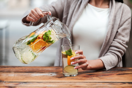 Healthy drink for healthy life. Close-up of young woman pouring fresh lemonade to glass while standing at the wooden desk