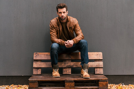 mode: Trygga och vacker. Stilig ung man sitta på träpall och tittar på kameran med grå vägg i bakgrunden och orange löv på golvet