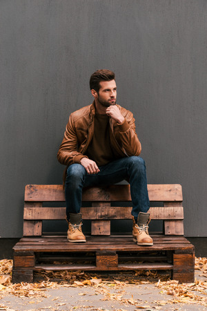 model: Lost in thoughts. Thoughtful young man sitting on the wooden pallet and looking away with grey wall in the background and orange fallen leaves on the floor