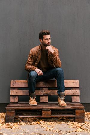 models posing: Perdido en pensamientos. Hombre joven pensativo sentado en la plataforma de madera y mirando de lejos con la pared gris en el fondo de las hojas y naranja ca�do en el suelo