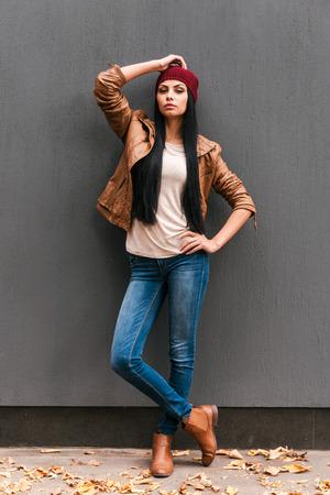 moda ropa: Casualmente bella. Mujer joven hermosa que presenta contra la pared gris con las hojas caídas que pone a su alrededor