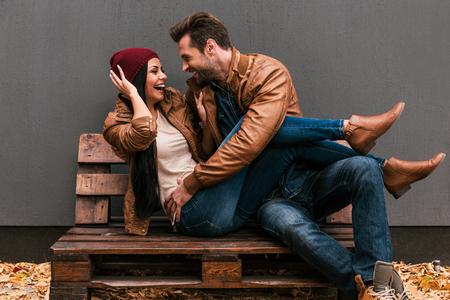 parejas romanticas: Pareja juguetona. Joven cari�osa pareja se divierte Juguet�n juntos mientras est� sentado en la plataforma de madera junto a la pared gris en el fondo y ca�do las hojas en el suelo ht Foto de archivo