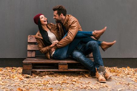 romantik: Carefree tid tillsammans. Vackra unga par att ha kul tillsammans sitter på träpall tillsammans med grå vägg i bakgrunden och nedfallna löv på ht golvet