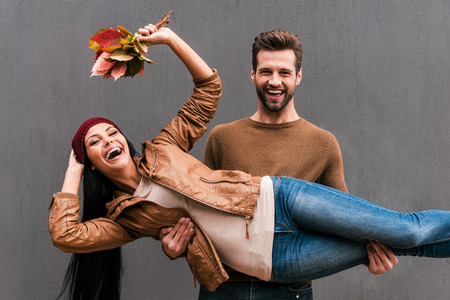 fashion style: Love and fun. Beautiful young couple having fun together while standing against grey wall