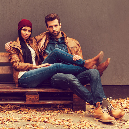 Autumn style. Beautiful young couple bonding to each other while sitting on the wooden pallet with grey wall in the background and fallen leaves laying on the floor