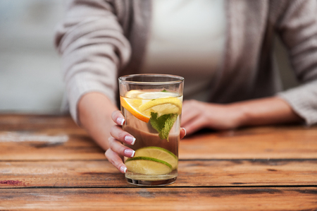 drink water: Enjoy freshness! Close-up of young woman stretching out glass with fresh lemonade while standing at the wooden desk Stock Photo
