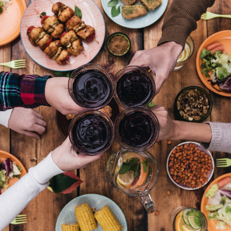 Cheers to friends! Top view of four people cheering with red wine while sitting at the rustic dining table