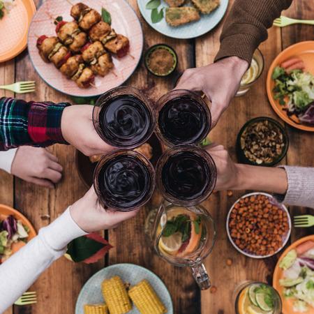 Juicht aan vrienden! Bovenaanzicht van de vier mensen juichen met rode wijn tijdens de vergadering op de rustieke eettafel