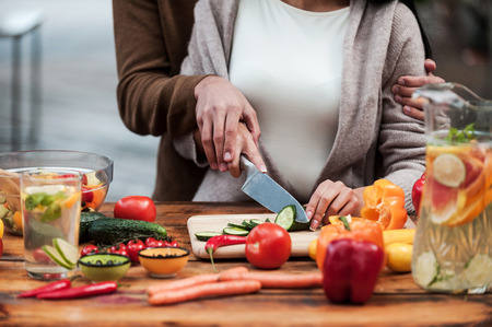 一緒に食品を準備しています。一緒に木製のテーブルの若いカップル カット野菜のクローズ アップ