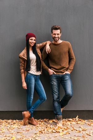 Jong en gratis. Mooie jonge paar binding aan elkaar en glimlachen terwijl leunend tegen de grijze muur met gevallen bladeren leggen om hen heen