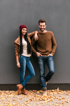 stylish hair: Young and free. Beautiful young couple bonding to each other and smiling while leaning at the grey wall with fallen leaves laying around them Stock Photo
