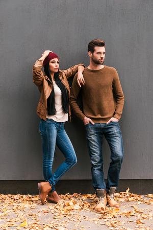 秋スタイルを楽しんでいます。互いに美しい若いカップルの結合とそれらの周り敷設落ち葉で灰色の壁にもたれて、よそ見