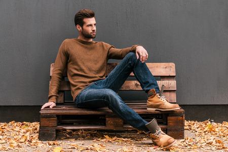 casual clothes: Casualmente guapo. Apuesto joven sentado en la plataforma de madera y mirando de lejos con la pared gris en el fondo de las hojas y naranja ca�do en el suelo