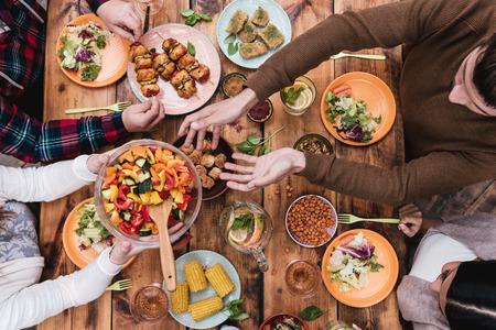 еда: Друзья обедал. Вид сверху из четырех человек, имеющих ужин вместе, сидя на деревенский деревянный стол