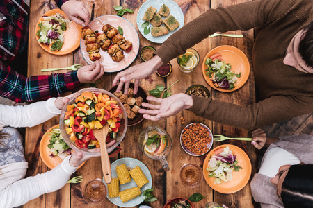 table: Friends having dinner. Top view of four people having dinner together while sitting at the rustic wooden table