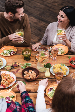 four people: Dining with friends. Top view of four people having dinner together while sitting at the rustic wooden table