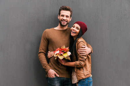 Young and carefree. Beautiful young couple bonding to each other and smiling while leaning at the grey wall