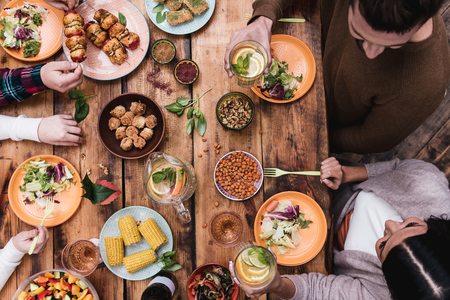 dinner table: Enjoying great dinner. Top view of four people having dinner together while sitting at the rustic wooden table Stock Photo
