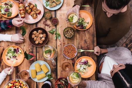 Godendo di grande cena. Vista dall'alto di quattro persone a cena insieme, seduti al tavolo di legno rustico