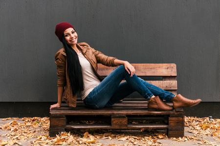 Trendy beauty. Beautiful young woman sitting on the wooden pallet and smiling with fallen leaves laying around her Stock Photo