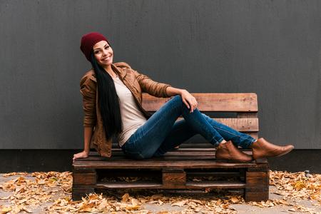 Trendy schoonheid. Mooie jonge vrouw zittend op de houten pallet en lachend met gevallen bladeren tot rond haar