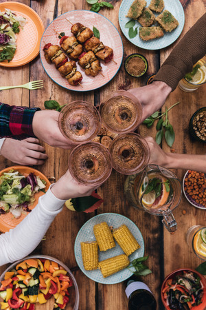dining table: Cheers to friends! Top view of four people cheering with wine while sitting at the rustic dining table Stock Photo