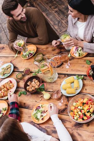 hombre comiendo: Cena con los mejores amigos. Vista superior de cuatro personas cenando juntos mientras se está sentado en la mesa de madera rústica