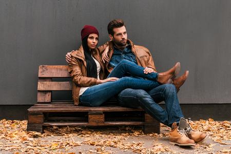 moda: Apreciando o tempo junto. Lindo casal jovem ligação um com o outro, sentado no estrado de madeira com parede cinza no fundo e folhas caídas no chão