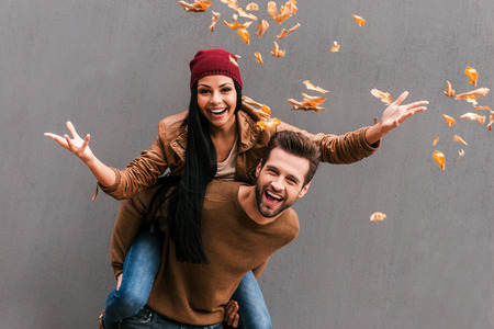 headwear: Carefree fun. Handsome young man piggybacking his girlfriend throwing orange fallen leaves an smiling ith grey wall as background Stock Photo