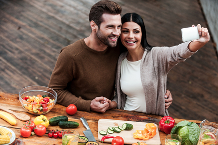 capturing: Capturing bright moments together. Top view of beautiful young couple making selfie and smiling while preparing food together Stock Photo