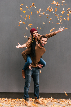 Autumn fun. Full length of handsome young man piggybacking his girlfriend throwing orange fallen leaves an smiling with grey wall as background