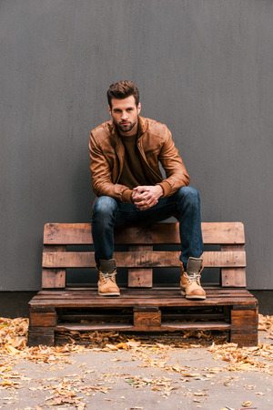 casually: Casually handsome. Handsome young man sitting on the wooden pallet and looking at camera with grey wall in the background and orange fallen leaves on the floor