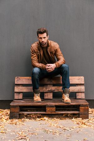 Casualmente guapo. Apuesto joven sentado en la plataforma de madera y mirando a cámara con una pared gris en el fondo y naranja hojas caídas en el suelo