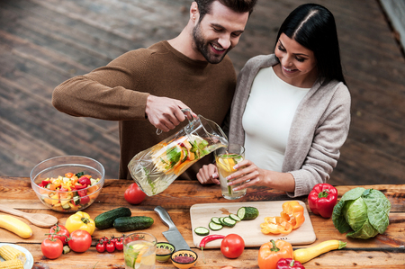 preparing food: Enjoying healthy food and drinks. Cheerful young man pouring fresh lemonade to his girlfriend while preparing food on the wooden desk together Stock Photo