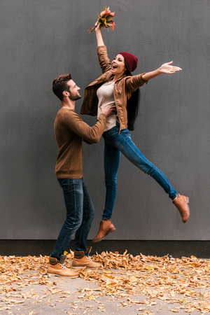 autumn young: Autumn fun. Beautiful young couple having fun together while standing against grey wall with orange fallen leaves laying around them