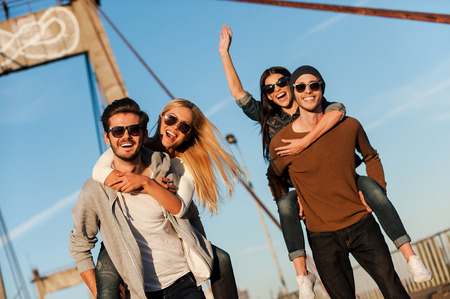 urban culture: We just want to have fun! Two handsome young men piggybacking their girlfriends and smiling while walking along the bridge