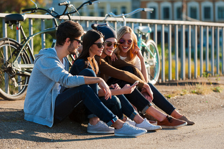 mobile phone: Relaxing after day riding. Group of young smiling people bonding to each other and looking at smart phone while sitting outdoors together with bicycles in the background