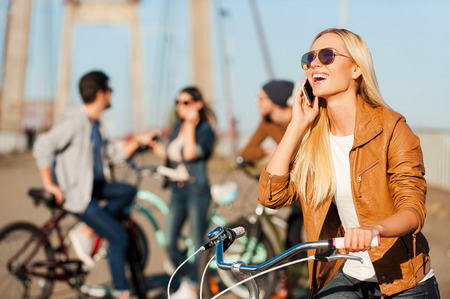 connect: Staying connected. Beautiful young smiling woman leaning at her bicycle and talking on the mobile phone while her friends standing in the background
