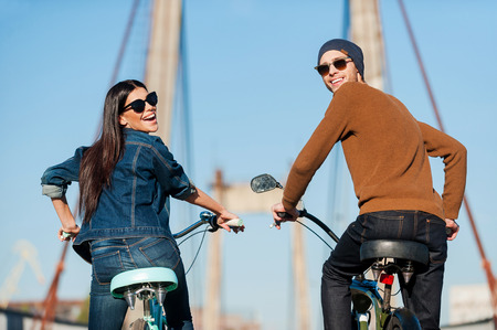 young happy couple: Enjoying fun ride. Rear view of beautiful young couple riding bicycles and looking over shoulder with smile