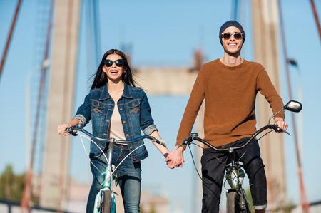 Disfrutando su fecha activa. Hermosa joven pareja andar en bicicleta a lo largo del puente y sonriendo Foto de archivo