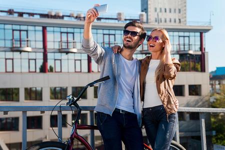 haciendo el amor: La captura de amor y diversi�n. Hermosa joven pareja haciendo selfie en su tel�fono inteligente y sonriendo mientras est� de pie cerca de la bicicleta al aire libre Foto de archivo