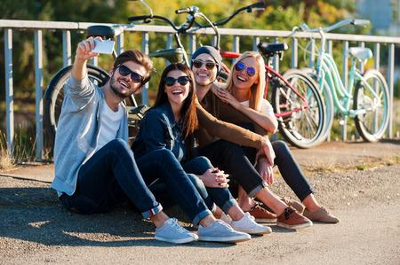재미를 잡아라. 백그라운드에서 자전거와 함께 야외에서 앉아있는 동안 서로 접착시키고 똑똑한 전화로 셀카를 만드는 젊은 웃는 사람들의 그룹 스톡 콘텐츠