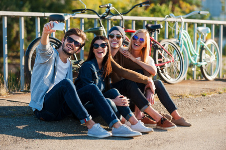 Capturing fun. Group of young smiling people bonding to each other and making selfie by smart phone while sitting outdoors together with bicycles in the background