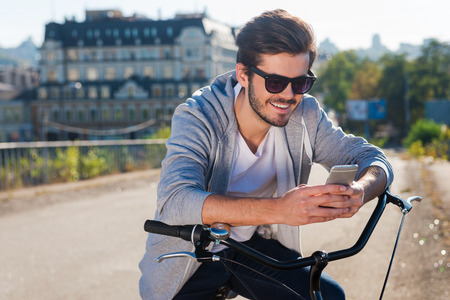 only one person: Inviting friend for a ride. Handsome young smiling man leaning at his bicycle and looking at his mobile phone while standing outdoors