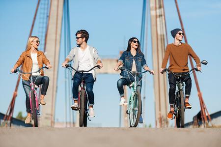 Passar um tempo despreocupado juntos. Quatro jovens andando de bicicleta ao longo da ponte e sorrindo