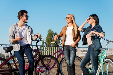 personas hablando: Compartiendo las últimas noticias con tus amigos. Tres jóvenes que hablan el uno al otro y sonriendo mientras se inclina en sus bicicletas al aire libre